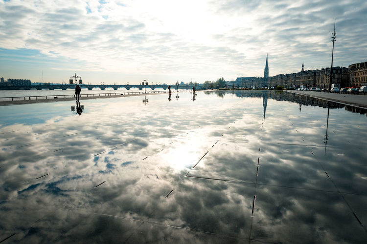 Clouds reflecting on calm lake in city