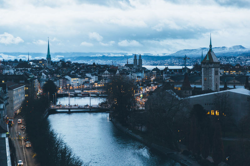 Aerial view of zurich city center at dawn, with the limmat river in the foreground.