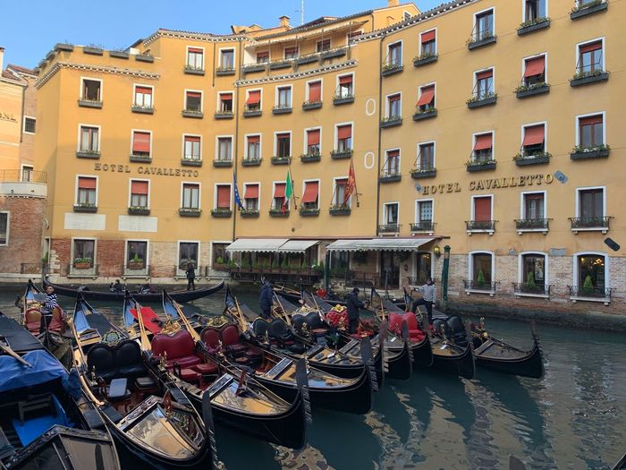 Boats moored in canal against buildings in city