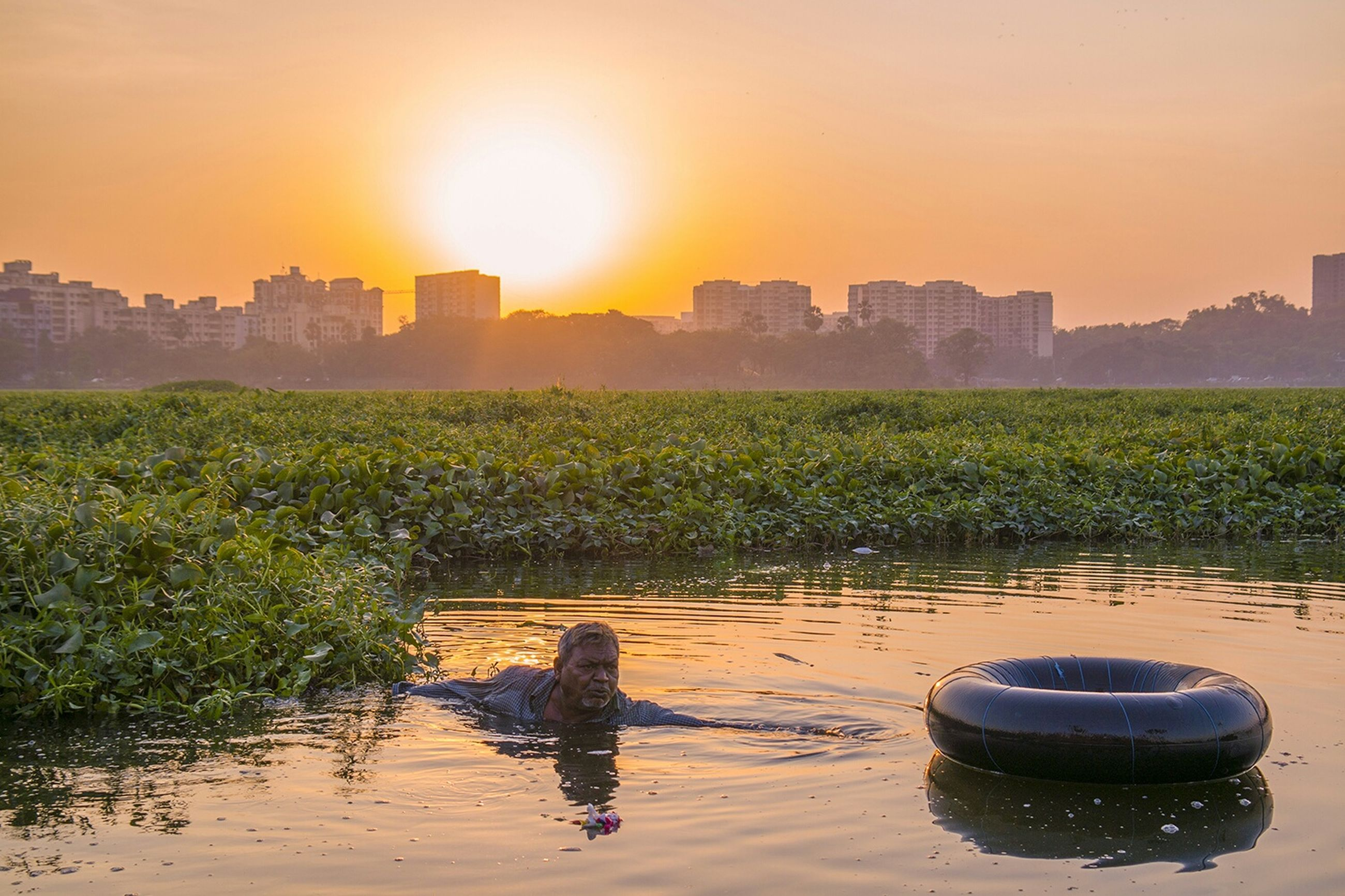 sunset, sun, water, architecture, built structure, building exterior, reflection, sunlight, grass, sky, nature, tranquil scene, tranquility, growth, waterfront, beauty in nature, scenics, river, orange color, plant