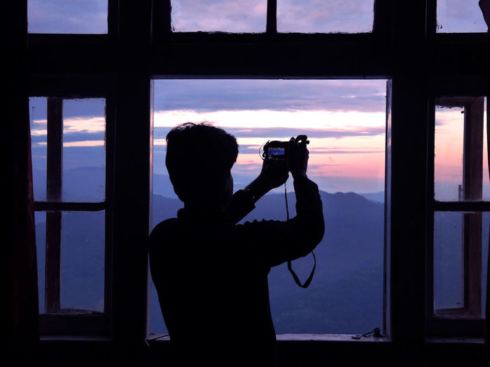 Rear view of silhouette man photographing through window