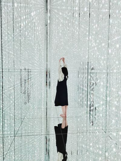 Side view of woman standing by glass wall