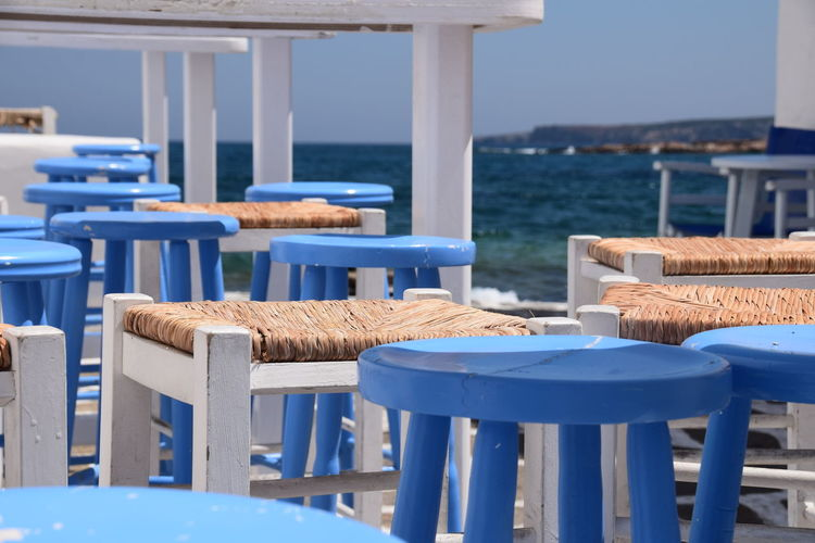 Chairs and tables at restaurant at paros