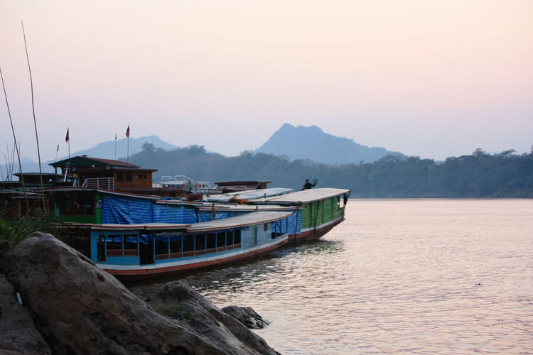 Boat on Mekong river - Laos Sky Water Mountain Nautical Vessel Transportation Mode Of Transportation Sunset Beauty In Nature Scenics - Nature Nature Architecture No People Tranquil Scene Moored Mountain Range Tranquility Sea Built Structure Clear Sky Outdoors Boat Mekong River Mekong Laos