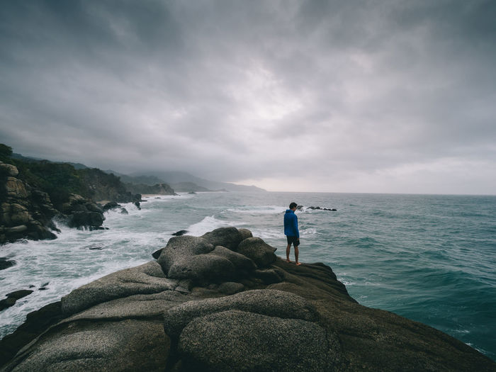 Rear view of man standing on rock by sea against cloudy sky
