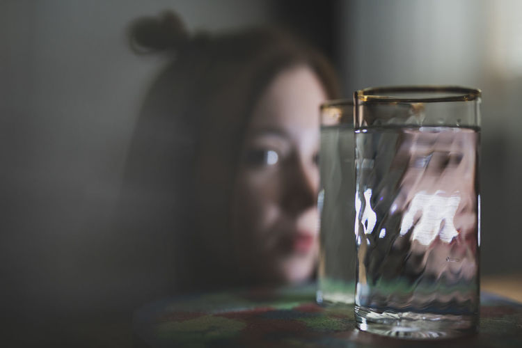 Close-up of woman looking through glass on table