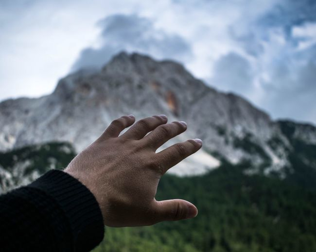 Close-up of human hand against mountain