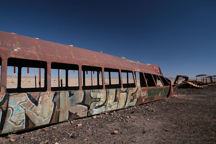Graffiti on abandoned train against clear blue sky