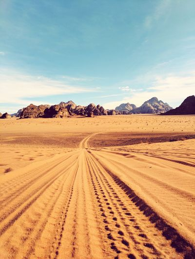 Scenic view of desert against blue sky during sunny day