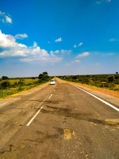 Road passing through car against sky