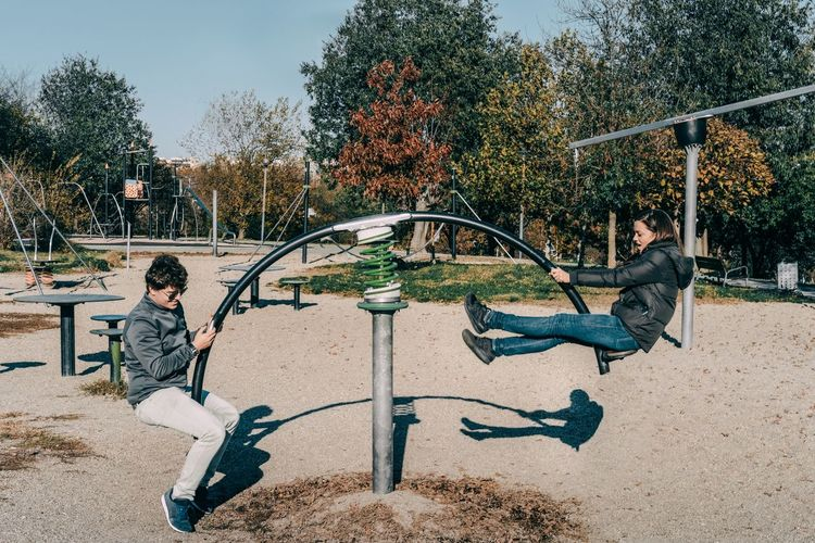 Side view of friends sitting on seesaw at playground