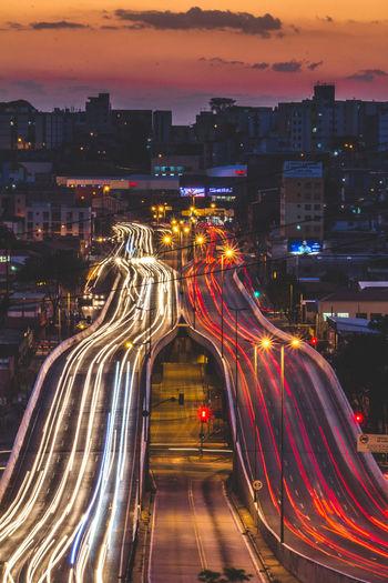 Light trails on bridge in city at dusk