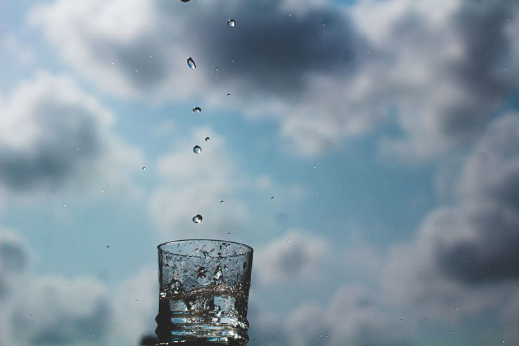 Water drops on glass against sky