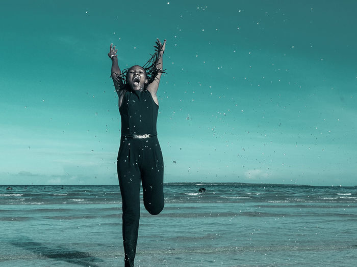 Full length of young woman with arms raised jumping in sea against sky