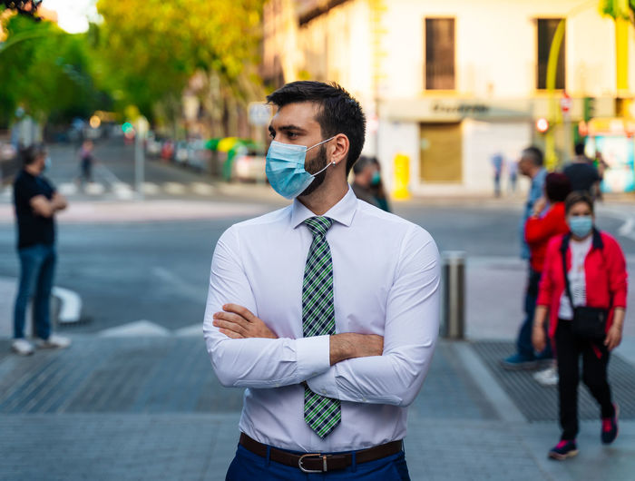 Young elegant businessman stands in middle of crowded street with surgical mask