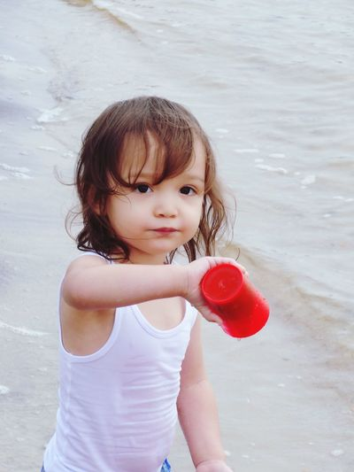 Portrait of cute girl holding red cup while standing at beach