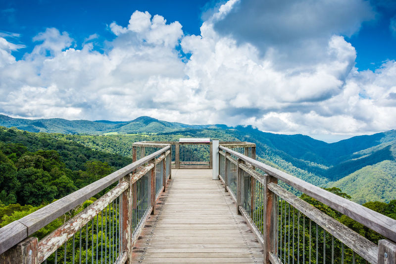 Boardwalk leading towards mountain against cloudy sky
