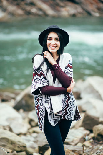 Portrait of smiling young woman standing on rock