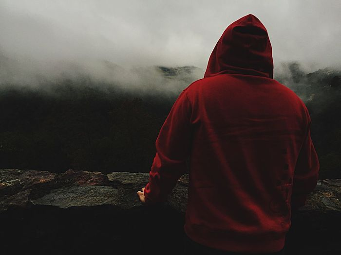 Rear View Of Man In Red Hooded Shirt Looking At Mountains During Foggy Weather