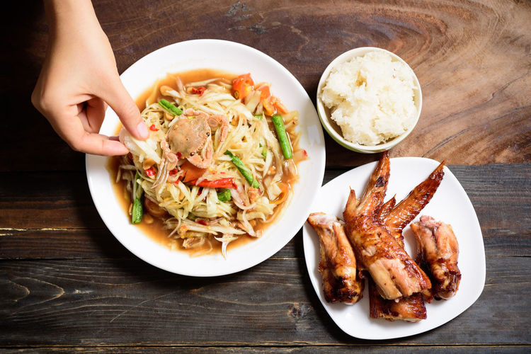 Spicy papaya salad Food Food And Drink Ready-to-eat Table Freshness Plate Meat Human Hand Indoors  Healthy Eating Serving Size Hand Human Body Part Wellbeing High Angle View Wood - Material Bowl Meal Vegetable Real People Spicy Papaya Salad Papaya Salad Thai Food Asian Food