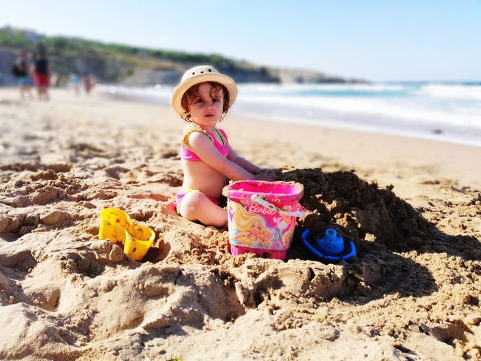 Portrait of cute baby girl playing on beach