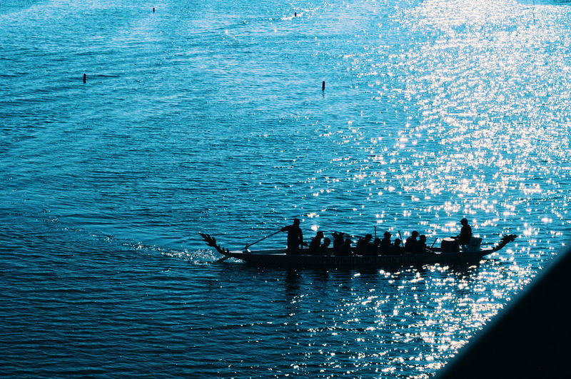 Silhouette people on boat in sea