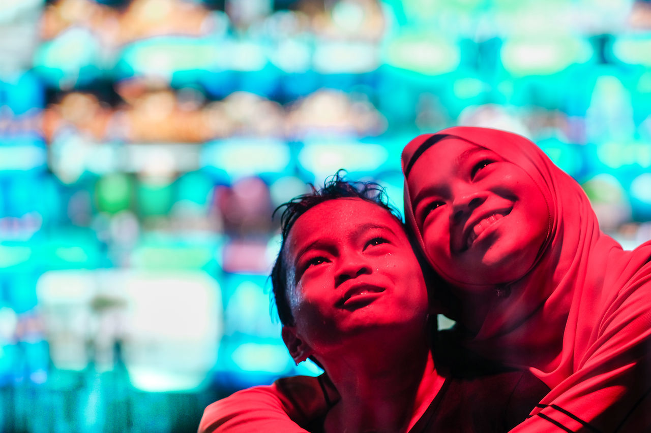 Thoughtful siblings standing in illuminated city at night