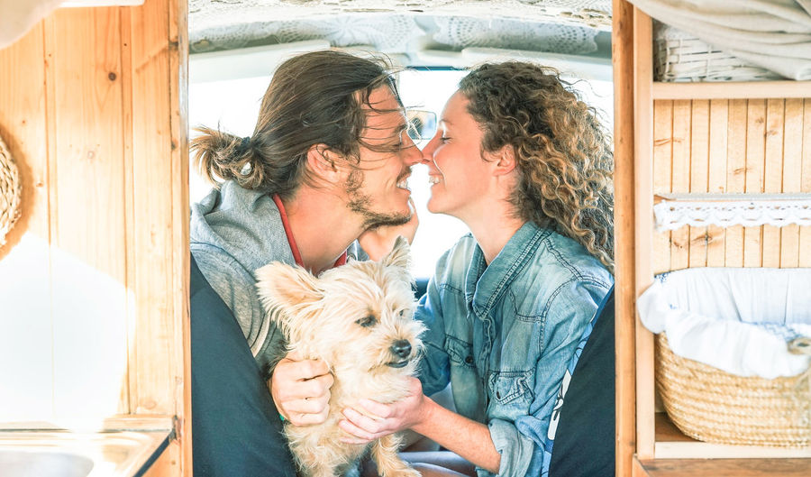 Happy couple with dog romancing in caravan