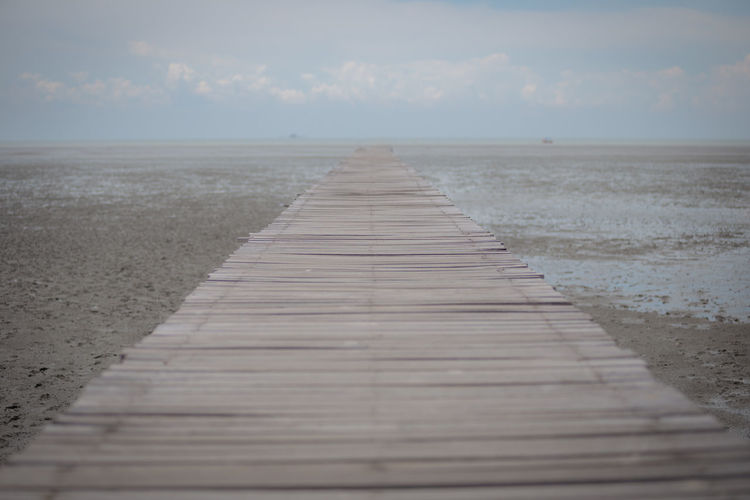 Surface level of wooden walkway at beach against sky