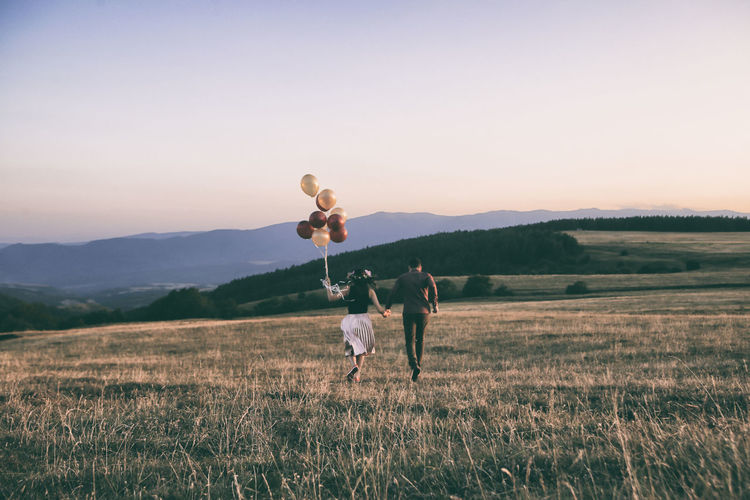 Young Couple Running With Balloons On Field Against Sky During Sunset