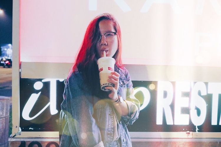 Young Woman Drinking While Standing Against Billboard At Night