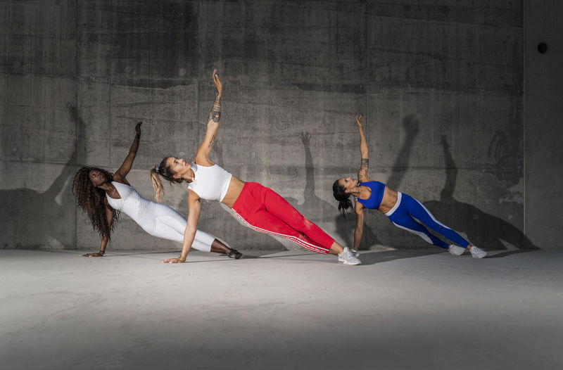 Three beautiful Caucasian and African American fitness female athletes exercising with a side plank in an open concrete stadium wearing bright sports wear, with shadows on the walls Exercising Stretching Women Fitness Girls Healthy Eating Training Fitness Model Beautiful Outdoors Stadium Atmosphere Workout Lifestyles Real People Brignt Active Young Women Sportswear Sunset Concrete Wall Concrete Structure Concrete Surface African Girl  Caucasian Girls Side Planks