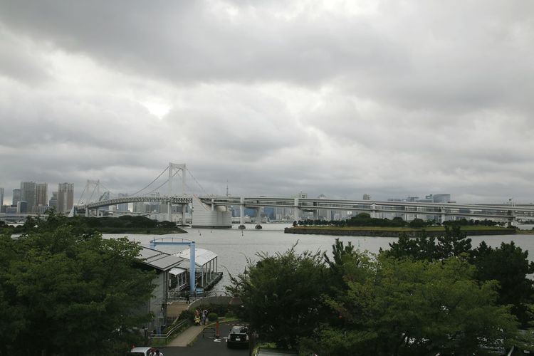 Suspension bridge in city against cloudy sky