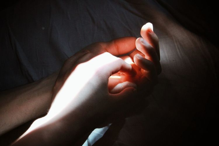 Close-up of human hands on bed