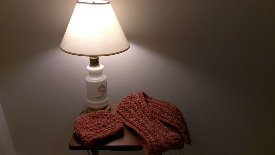 High angle view of woolen cloth by electric lamp at home