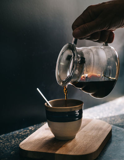 Cropped image of hand pouring coffee cup on table