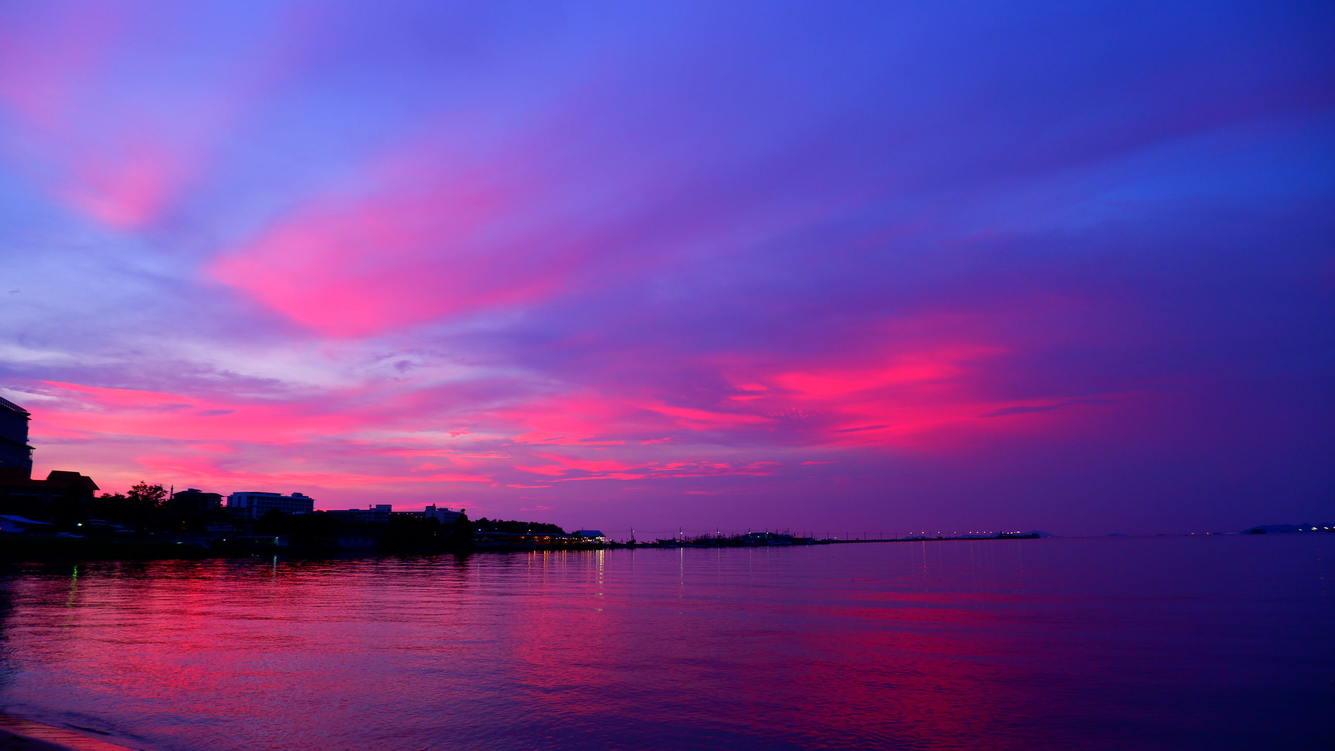 water, sky, afterglow, sunset, beauty in nature, cloud, sea, scenics - nature, horizon, dawn, reflection, nature, tranquility, tranquil scene, no people, architecture, evening, landscape, red sky at morning, multi colored, travel destinations, dramatic sky, outdoors, city, pink, idyllic, silhouette, purple, night, blue, environment, beach, magenta, travel, land, built structure