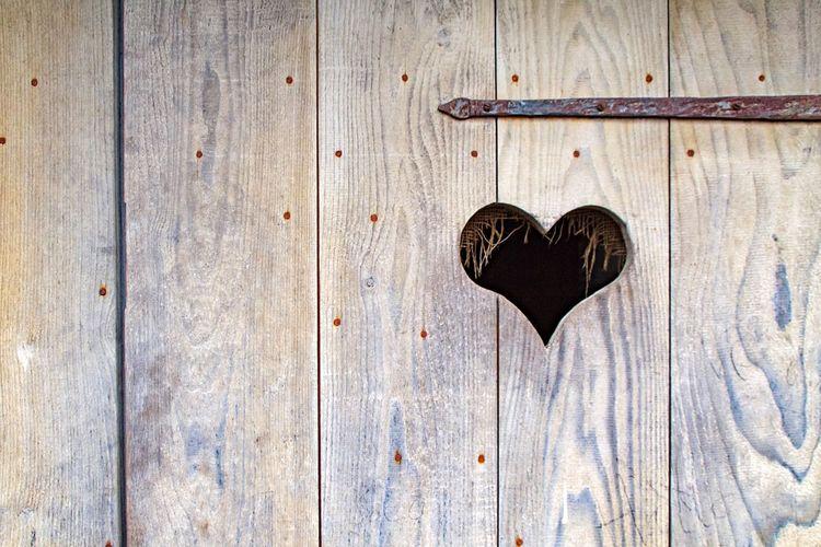 Heart shape amidst wooden wall