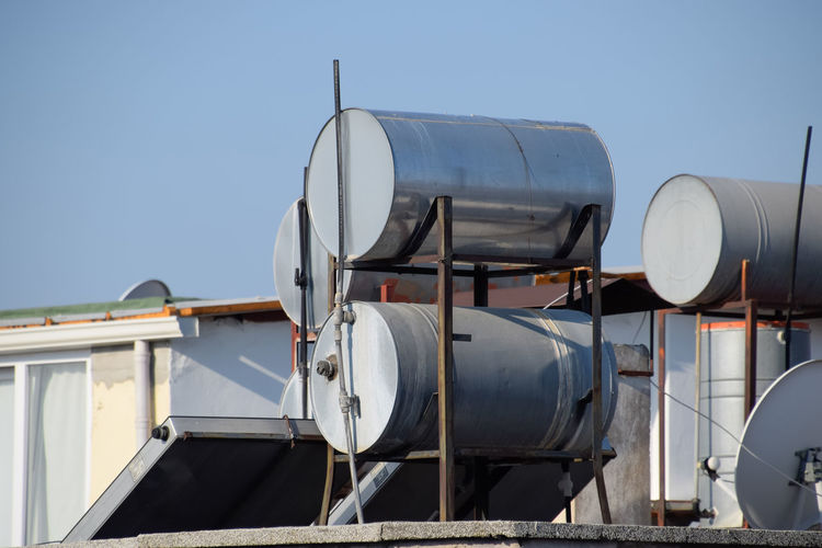 Antalya, Turkey - May 19, 2019: Steel barrels of boilers with water on the roof of a building to heat water. Water heating by the sun and solar panels. Steel Barrels Boilers Water Roof Building Heating Sun Solar Batteries Alternative Own Independent  HEAD Cylinder Barrel Ten Free Turkey Antalya Vessel Water Supply Utilities Antennas Satellite Digital Tv Communications Plates
