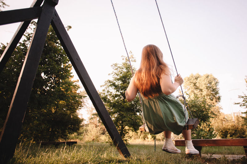 Rear view of woman on swing against sky