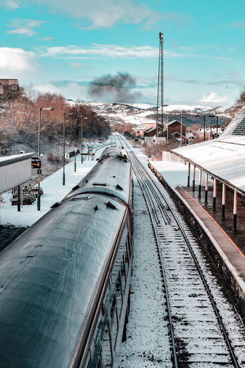 Train at railroad station against sky during winter