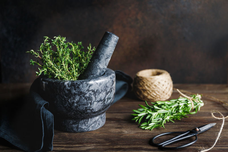 Close-up of mortar and pestle with herbs on table