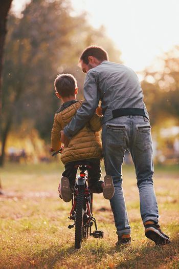 Family life Family With One Child Father Son Childhood Boys Park - Man Made Space Togetherness Lifestyles Learning Leisure Activity Outdoors Adult Men Fall Season Fall Colors Father's Day Autumn Collection Fatherhood  Father & Son Family Autumn Colors Fatherhood Moments Fun Cycling Bicycle