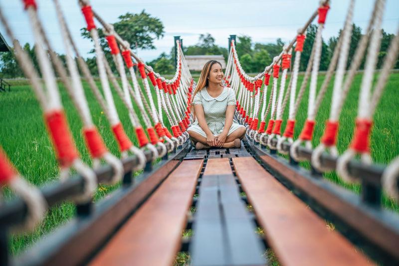 Happy woman looking away while sitting on footbridge