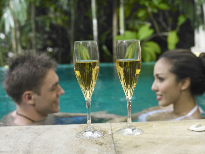 Close-Up Of Drink At Poolside With Couple In Swimming Pool