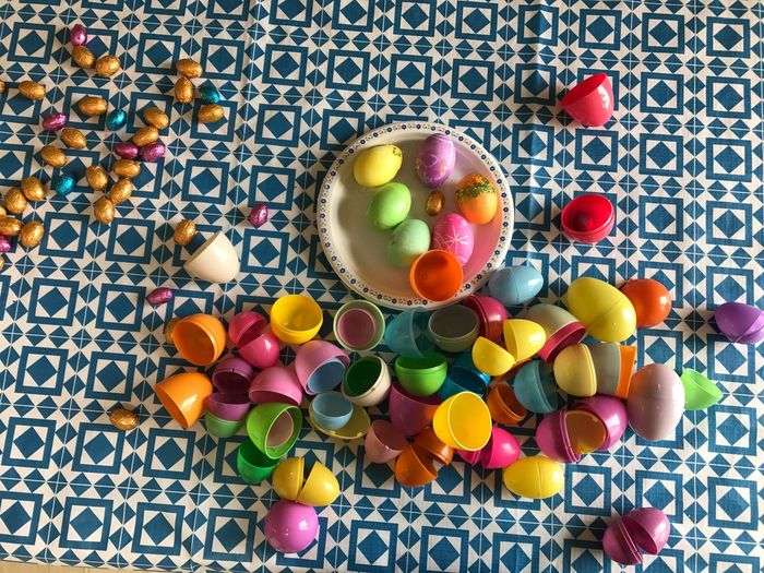 High Angle View Of Colorful Easter Eggs With Chocolates On Table