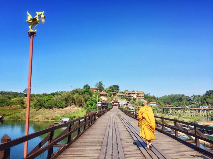 Rear view of a monk walking on footbridge