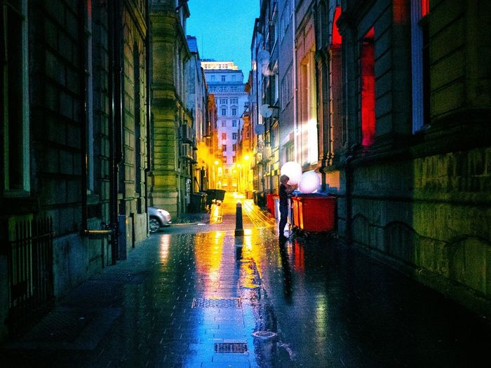Man walking on wet road in city at night