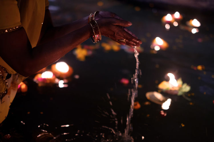 Pray at the Ganges River Burning Candle Celebration Close-up Diwali Diya - Oil Lamp Flame Focus On Foreground Glowing Heat - Temperature Holding Hope Human Body Part Human Hand Illuminated Night Oil Lamp One Person Outdoors Place Of Worship Real People Religion Spirituality Tradition Women