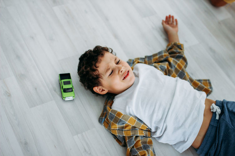 High angle view of boy lying on floor at home